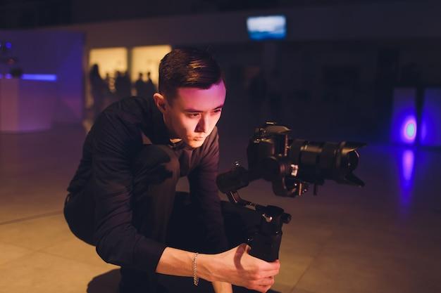 Profesjonalny kamerzysta trzymający kamerę na 3-osiowym gimbalu. kamerzysta używa steadicamu. profesjonalne urządzenia pomagają tworzyć wysokiej jakości filmy bez wstrząsania.