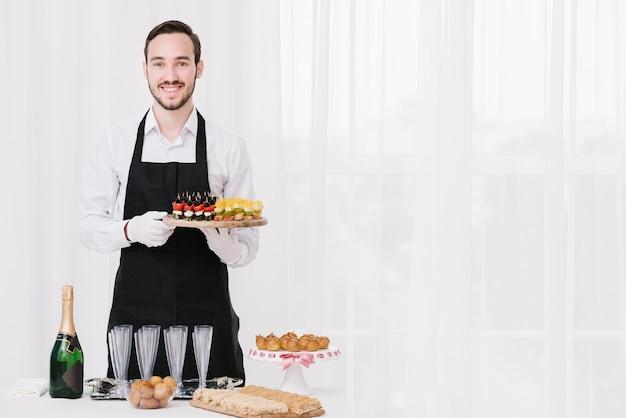 Profesjonalny kelner prezentujący jedzenie