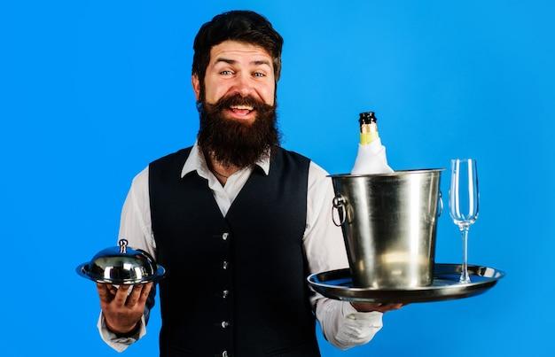 Profesjonalny kelner w mundurze z tacą do serwowania i chłodziarką do wina. obsługa restauracji.