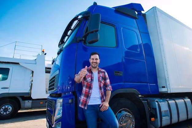 Profesjonalny kierowca ciężarówki przed długim pojazdem transportowym, trzymając kciuki do góry, gotowy do nowej przejażdżki