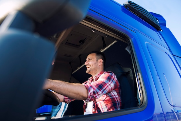 Profesjonalny kierowca ciężarówki w średnim wieku w kabinie jazdy ciężarówką i uśmiechnięty