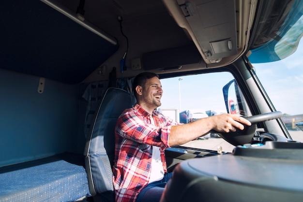 Profesjonalny kierowca ciężarówki w średnim wieku w zwykłym ubraniu prowadzący pojazd ciężarowy i dostarczający ładunek do miejsca przeznaczenia