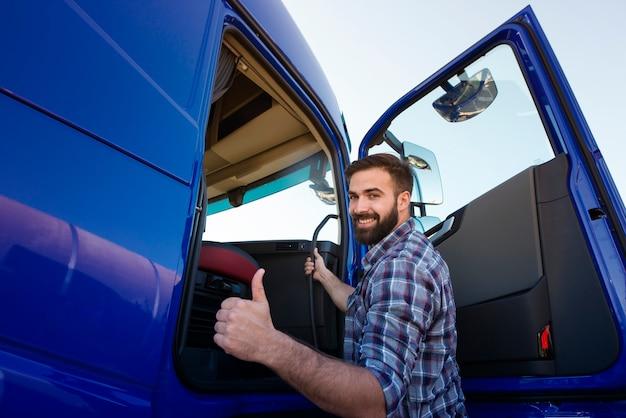 Profesjonalny kierowca ciężarówki wchodzący do jego długiego pojazdu ciężarówki i trzymając kciuki do góry