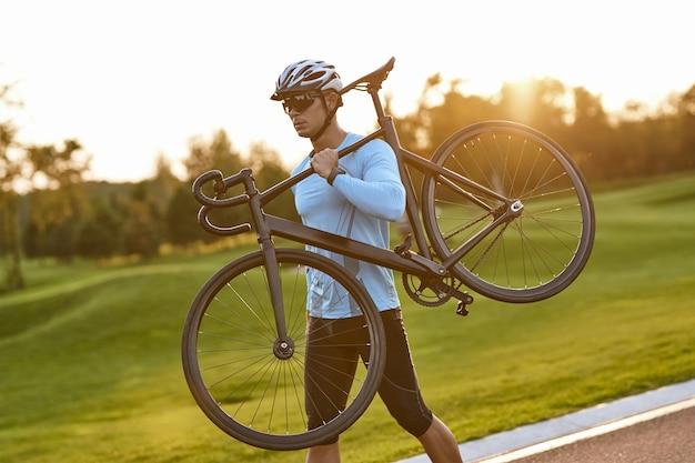 Profesjonalny kolarz szosowy silny wysportowany mężczyzna w odzieży sportowej i kasku ochronnym niosącym jego
