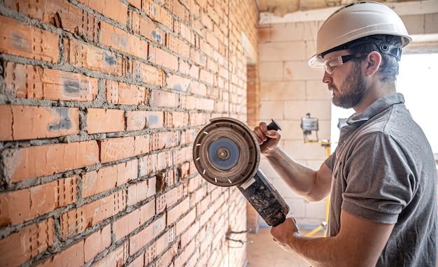 Profesjonalny konstruktor odzieży roboczej pracuje z narzędziem tnącym.