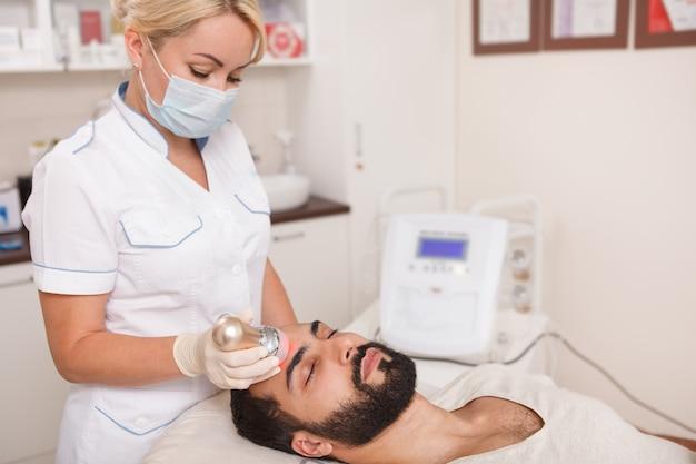 Profesjonalny kosmetolog wykonujący zabieg rf-lifting twarzy dla klienta płci męskiej, miejsce na kopię