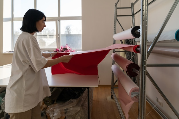Profesjonalny krawiec dziewczyna wybiera rolkę tkaniny do cięcia designerskiego materiału do projektowania ubrań
