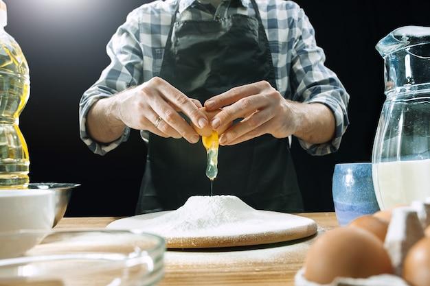 Profesjonalny kucharz męski posypuje ciasto mąką