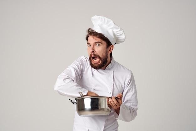 Profesjonalny kucharz męski w restauracji z rondelkiem w rękach obsługi