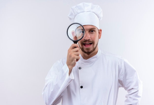 Profesjonalny kucharz mężczyzna w białym mundurze i kapelusz kucharz patrząc na camra przez szkło powiększające uśmiechnięty wesoło stojąc na białym tle