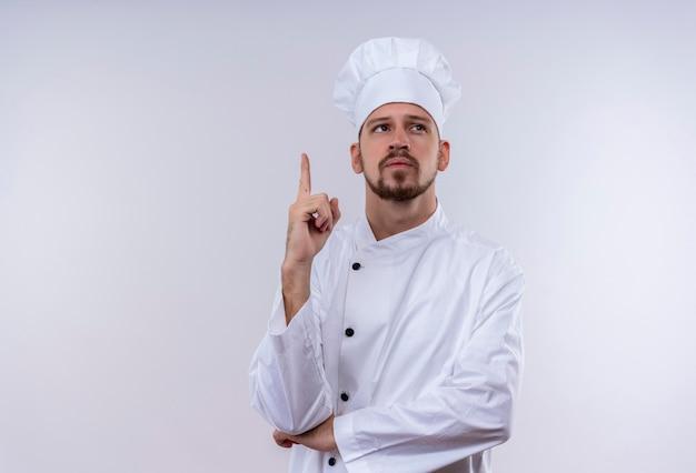 Profesjonalny kucharz mężczyzna w białym mundurze i kapelusz kucharz skierowany w górę z palcem wskazującym, patrząc pewny siebie, mając świetny nowy pomysł stojący na białym tle