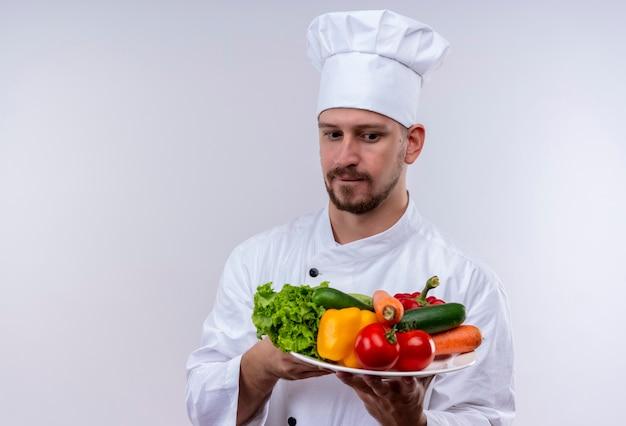Profesjonalny kucharz mężczyzna w białym mundurze i kapelusz kucharz trzyma talerz z warzywami patrząc na nich zaintrygowany stojąc na białym tle