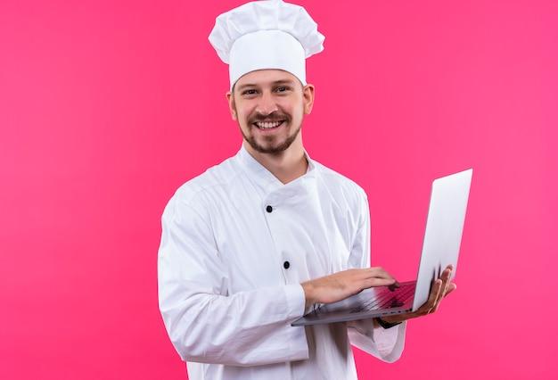 Profesjonalny kucharz mężczyzna w białym mundurze i kapelusz kucharz trzymając laptopa patrząc na kamery uśmiechnięty wesoły stojąc na różowym tle