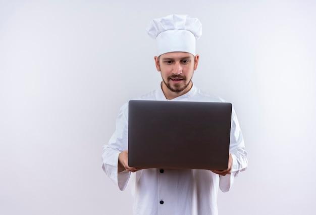 Profesjonalny kucharz mężczyzna w białym mundurze i kapelusz kucharz trzymając laptopa patrząc na to zaintrygowany stojąc na białym tle