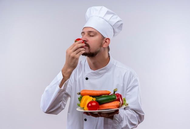 Profesjonalny kucharz mężczyzna w białym mundurze i kapelusz kucharz, trzymając talerz z warzywami, wdycha zapach pomidora stojącego na białym tle