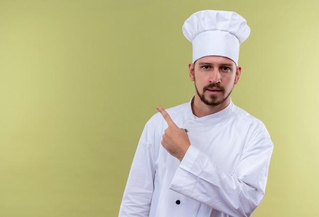 Profesjonalny kucharz mężczyzna w białym mundurze i kapelusz kucharz wskazujący palcem w bok, patrząc pewnie stojąc na zielonym tle
