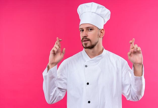 Profesjonalny kucharz mężczyzna w białym mundurze i kapeluszu kucharskim sprawia, że pożądane życzenie trzyma kciuki stojąc na różowym tle