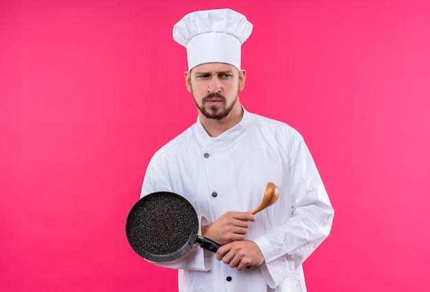 Profesjonalny kucharz mężczyzna w białym mundurze i kapeluszu kucharskim trzyma patelnię i drewnianą łyżkę patrząc na bok niezadowolony i marszczący brwi stojąc na różowym tle