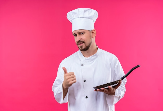Profesjonalny kucharz mężczyzna w białym mundurze i kapeluszu kucharz trzyma patelnię patrząc na kamery z pewnym uśmiechem pokazując kciuki do góry stojąc na różowym tle