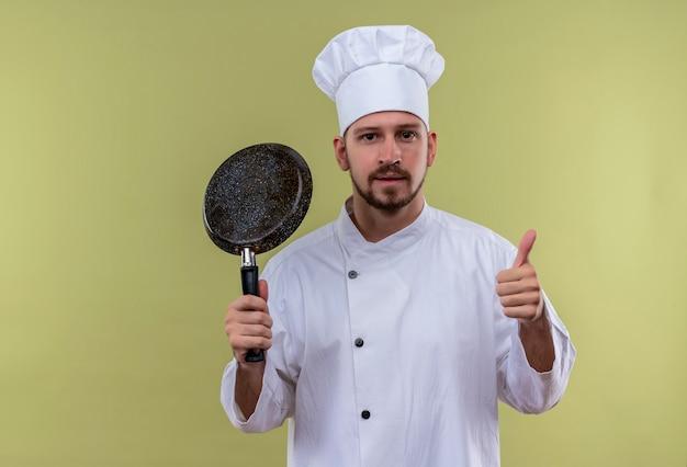 Profesjonalny kucharz mężczyzna w białym mundurze i kapeluszu kucharz trzyma patelnię patrząc pewnie pokazując kciuki do góry stojąc na zielonym tle
