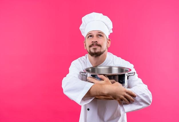 Profesjonalny kucharz mężczyzna w białym mundurze i kapeluszu kucharz trzyma pustą patelnię patrząc w górę z marzycielskim spojrzeniem stojącym na różowym tle