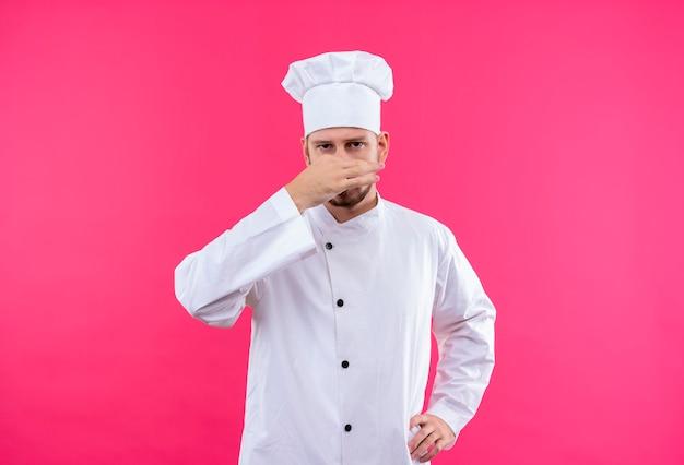 Profesjonalny kucharz mężczyzna w białym mundurze i kapeluszu kucharz zamykającym nos, koncepcja nieprzyjemnego zapachu na różowym tle