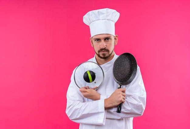 Profesjonalny kucharz mężczyzna w białym mundurze i kapeluszu, trzymając patelnię i pokrywkę rondla, patrząc pewnie stojąc na różowym tle
