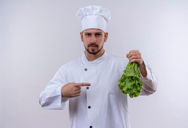Profesjonalny kucharz mężczyzna w białym mundurze i kucharz kapelusz trzymając sałatę, wskazując palcem na to, patrząc pewnie stojąc na białym tle