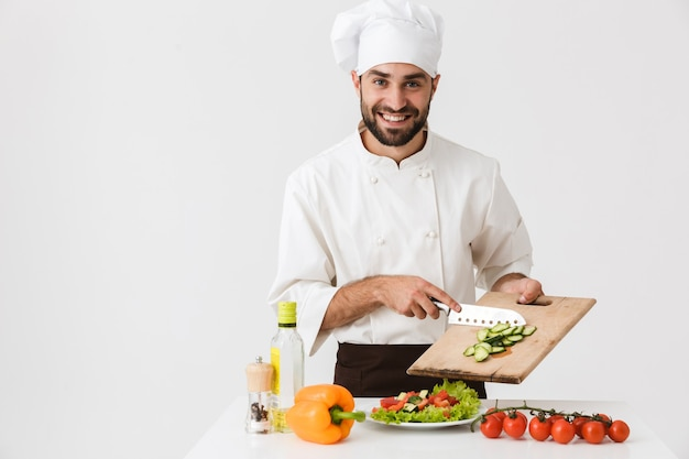Profesjonalny kucharz w mundurze uśmiechający się i krojący sałatkę warzywną na drewnianej desce odizolowanej nad białą ścianą