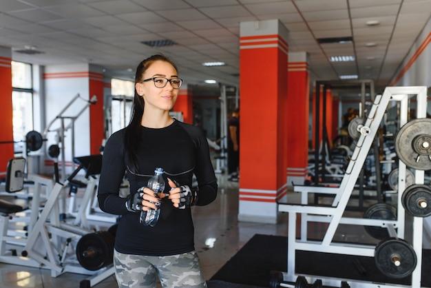 Profesjonalny kulturysta odpręża się po wyczerpującym treningu. sportowiec odpoczywa i pije wodę ze sportowej butelki we wnętrzu siłowni.