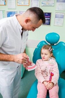 Profesjonalny lekarz, dentysta dziecięcy uczy dziecko mycia zębów. gabinet stomatologiczny do badania pacjenta. proces leczenia stomatologicznego u dziecka.