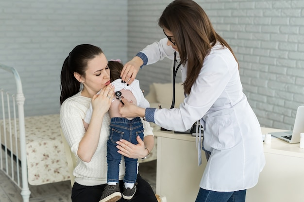 Profesjonalny lekarz ogólny pediatra w białej jednolitej sukni słucha dźwięku płuc i serca pacjenta dziecka ze stetoskopem.