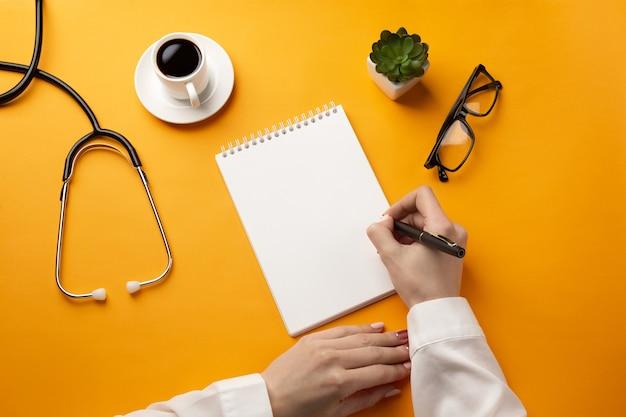 Profesjonalny lekarz pisania dokumentacji medycznej w zeszycie ze stetoskopem, filiżanką kawy i okularami. widok z góry z miejscem na twój tekst.