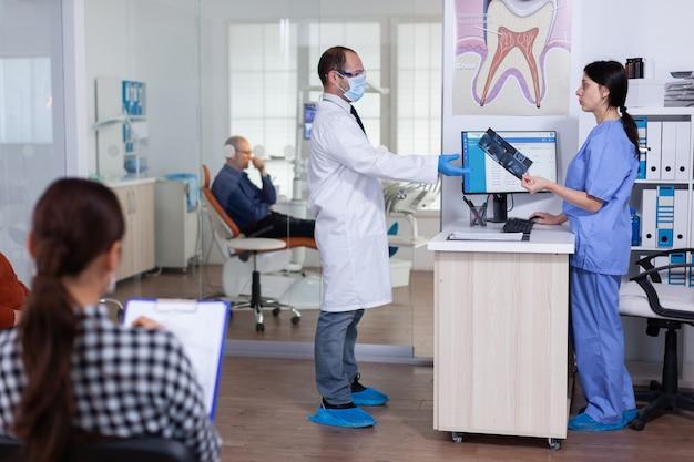 Profesjonalny lekarz proszący o prześwietlenie zębów przed badaniem pacjenta, podczas gdy osoby oczekujące w recepcji...