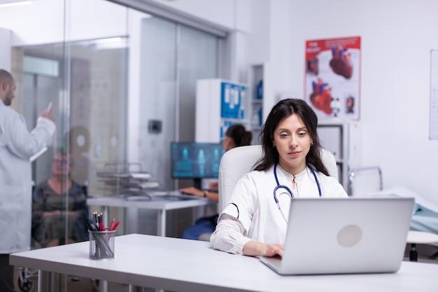 Profesjonalny lekarz w białym fartuchu pracujący na laptopie w nowoczesnej sali biurowej szpitala, terapeuta piszący na komputerze konsultuje się z pacjentem online, przeprowadza badania, analizuje informacje o wynikach z internetu
