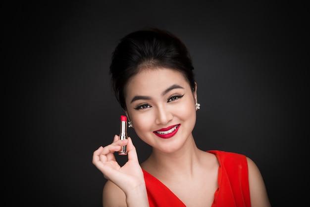 Profesjonalny makijaż. atrakcyjny model azjatycki stosując czerwoną szminkę.
