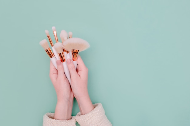 Profesjonalny makijaż pędzel kosmetyczny w kosmetyczki kobiece strony na tle mięty neo. widok z góry poziomej lato