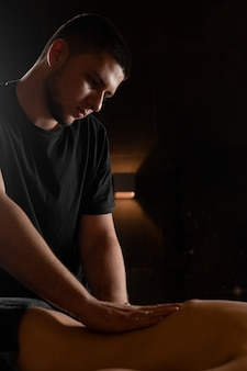 Profesjonalny masażysta wykonuje masaż pleców. terapia manualna. modelka relaksuje się na klasycznym zabiegu masażu w spa.