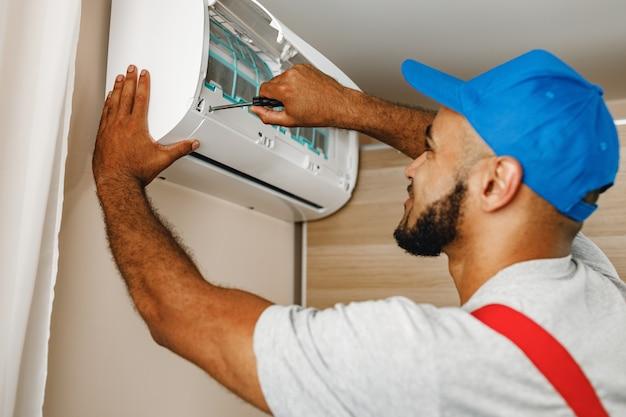 Profesjonalny mechanik instalujący klimatyzator w pokoju z bliska