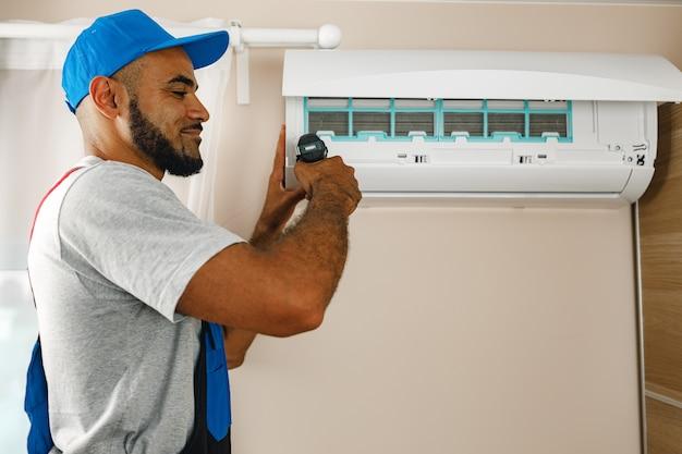Profesjonalny mechanik instalujący klimatyzator w pokoju