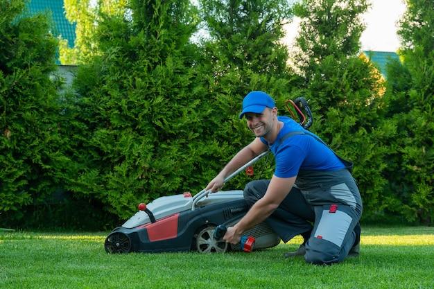 Profesjonalny mechanik naprawia kosiarkę mężczyzna naprawia kosiarkę na swoim podwórku