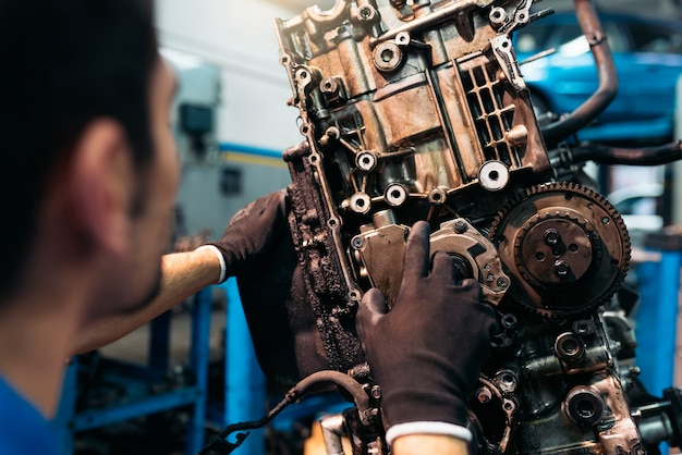 Profesjonalny mechanik naprawiający silnik samochodu w garażu.