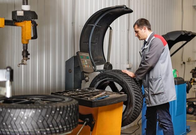 Profesjonalny mechanik samochodowy montaż opon z kolcami na wyważarce w warsztacie samochodowym.