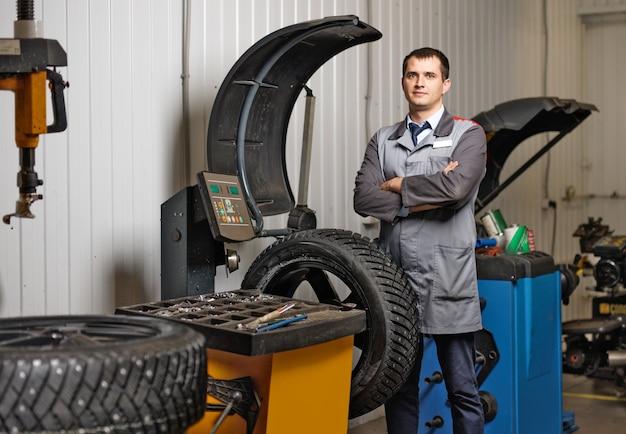Profesjonalny mechanik samochodowy montaż opon zimowych w serwisie samochodowym.