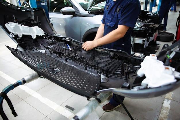 Profesjonalny mechanik samochodowy naprawia samochód na stacji obsługi i używa specjalnych narzędzi