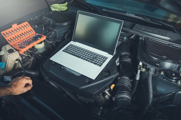 Profesjonalny mechanik samochodowy pracujący w serwisie auto naprawy za pomocą laptopa w samochodzie