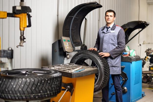 Profesjonalny mechanik samochodowy wyważający koło samochodowe na wyważarce w warsztacie samochodowym.