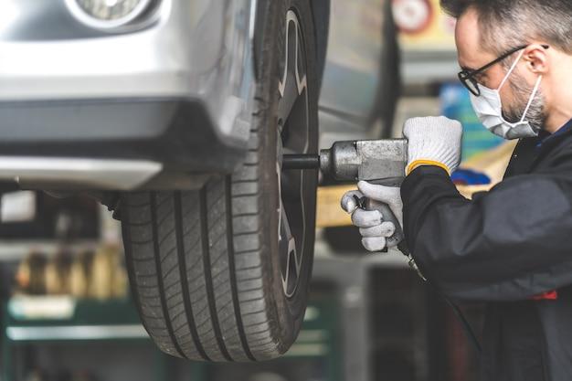 Profesjonalny mechanik samochodowy zmieniający koło samochodowe w warsztacie samochodowym i serwisowym