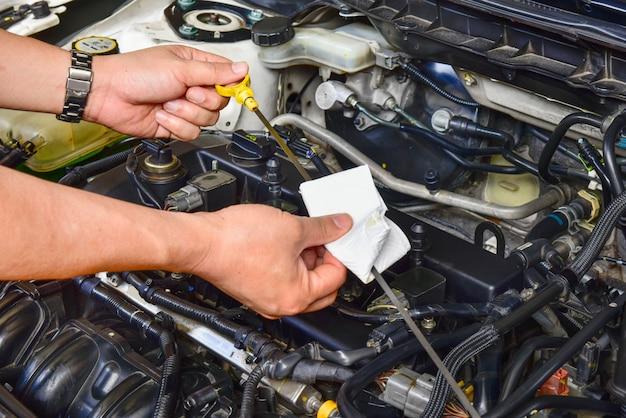 Profesjonalny mechanik trzyma miarkę poziomu oleju i sprawdza poziom oleju w silniku samochodu