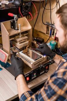 Profesjonalny mechanik w rękawicach ochronnych używający sprzętu do naprawy gadżetów, aby dowiedzieć się, na czym polega problem